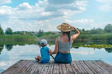 woman and boy sitting on dock holding fishing rod web